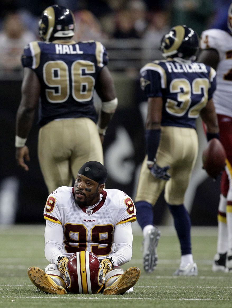 ASSOCIATED PRESS Washington Redskins wide receiver Santana Moss (89) sits on the field as St. Louis Rams' James Hall (96) and Bradley Fletcher (32) celebrate in the background after Fletcher intercepted a pass intended for Moss during the fourth quarter of an NFL football game Sunday, Sept. 26, 2010, in St. Louis. The Rams won 30-16.