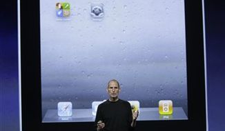 FILE - In this Sept. 1, 2010 file photo, Apple CEO Steve Jobs poses in front of an iPad display at an Apple announcement in San Francisco. (AP Photo/Paul Sakuma, file)