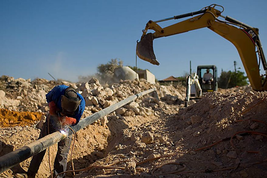 **FILE** A Palestinian man works at a construction site on Sept. 27 in the West Bank Jewish settlement of Yakir, south of the Palestinians town of Nablus. (Associated Press)