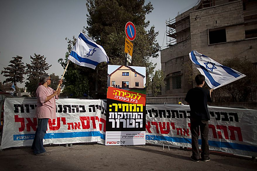 """Israeli activists of the 'Peace Now' movement wave Israeli flags as they stand next to placards, calling for the continuation of the construction slowdown in the West Bank settlements, during a protest outside Israel's Prime Ministerial residence, Sunday, Sept. 26, 2009. With a midnight deadline looming, Israel's prime minister on Sunday called on West Bank settlers to """"show restraint"""" after the end of a government-ordered construction slowdown, attempting to lower tensions with the Palestinians and prevent a breakdown in newly relaunched Mideast talks. (AP Photo/Oded Balilty)"""