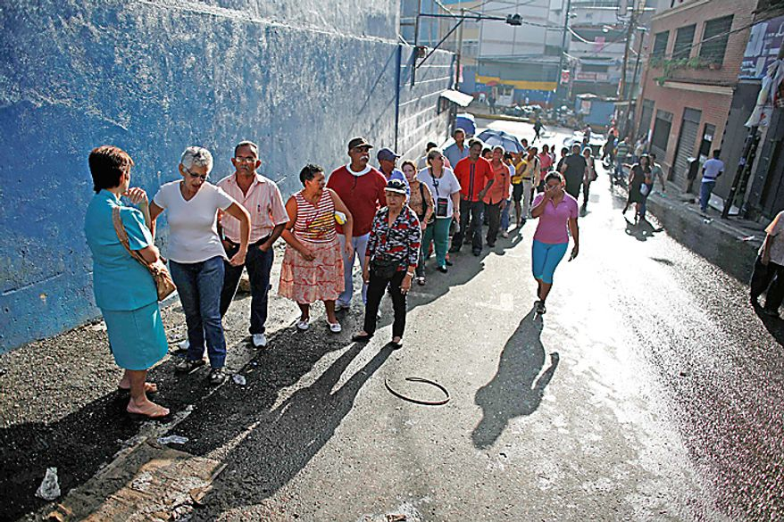 Voters wait in line to cast their ballots during congressional elections outside a polling station in Caracas, Venezuela, Sunday, Sept. 26, 2010. (AP Photo/Ariana Cubillos)