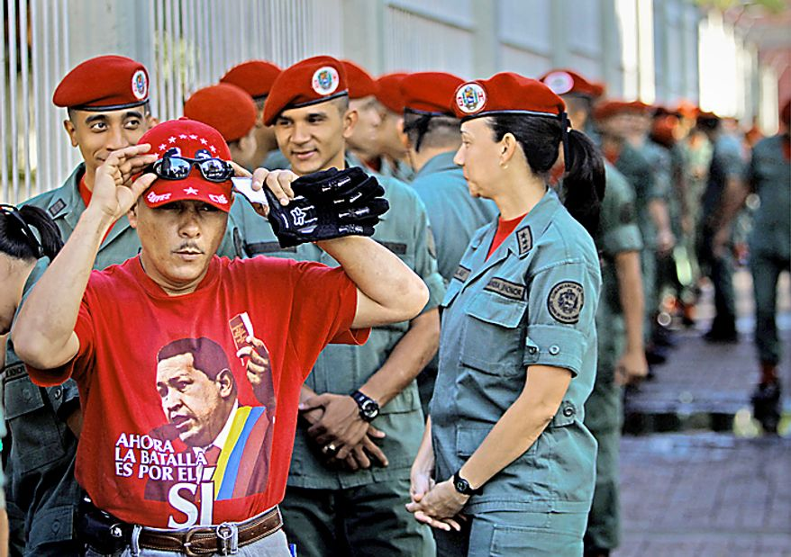"""A voter wearing a t-shirt that reads in Spanish: """" Now the battle is for YES"""", adjusts his sun glasses next to soldiers who line up outside a polling station during congressional elections in Caracas, Venezuela, Sunday, Sept. 26, 2010. (AP Photo/Fernando Llano)"""