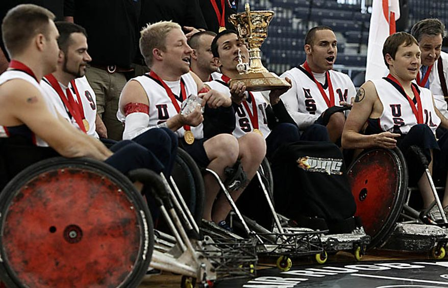 United States' Will Groulx, center, hoists the trophy after the U.S. team defeated Australia in the gold-medal match at the World Wheelchair Rugby Championships in Richmond, British Columbia, on Sunday, Sept. 26, 2010. (AP Photo/The Canadian Press, Darryl Dyck)