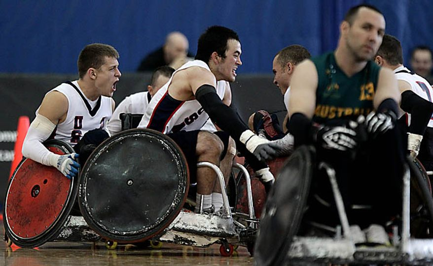 USA's Seth McBride, left to right, Chuck Aoki and Jason Regier, partially hidden, celebrate their gold medal win as Australia's Cameron Carr, right, leaves the court at the World Wheelchair Rugby Championships in Richmond, British Columbia, on Sunday Sept. 26, 2010. (AP Photo/The Canadian Press, Darryl Dyck)