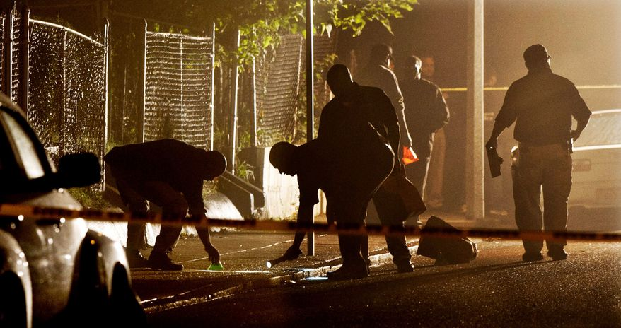 Boston Police detectives search for evidence after a pre-dawn shooting Tuesday in which four people, including a toddler, were fatally shot and a fifth sustained life-threatening injuries. Boston has experienced a spike in violent crime this year. (Associated Press)