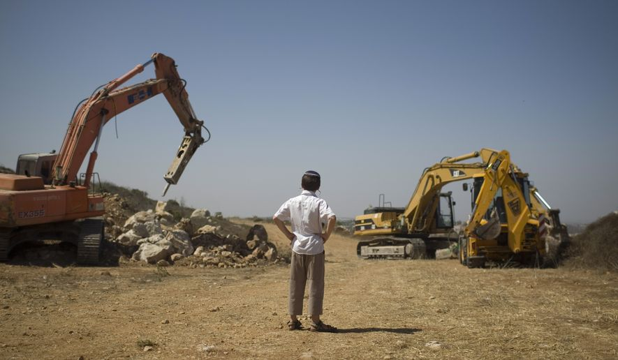 A Jewish settler boy watches earth-moving equipment working at a construction site in the West Bank Jewish settlement of Ariel on Monday, Sept. 27, 2010. Senior Palestinian official Yasser Abed Rabbo said Monday that President Mahmoud Abbas remains ready to walk out on Mideast peace talks if Israel resumes construction in its West Bank settlements now that building restrictions have expired. (AP Photo/Ariel Schalit)