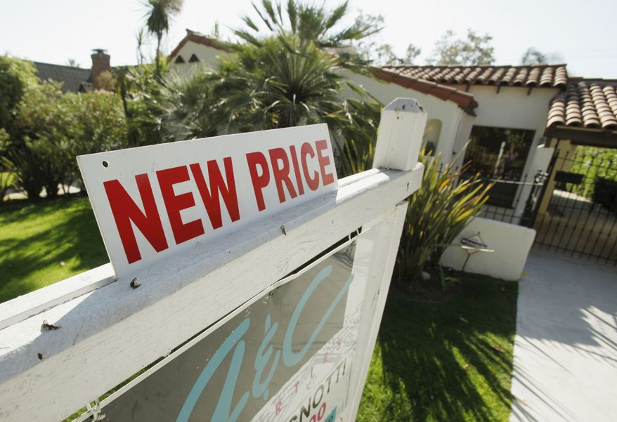 "A real estate agent's sign indicates a ""new price"" for a house in Glendale, Calif., on Saturday, Sept. 18, 2010. (AP Photo/Reed Saxon)"