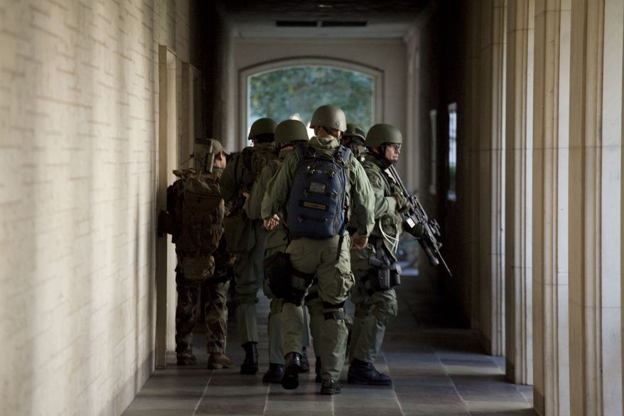 Soldiers prepare to enter Calhoun Hall at the University of Texas in Austin, Texas, on Tuesday Sept. 28, 2010. A gunman opened fire Tuesday inside the Perry-Castaneda Library then fatally shot himself, and police are searching for a possible second suspect, university police said. (AP Photo/The Daily Texan, Tamir Kalifa)