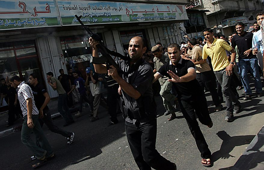 A relative of Palestinian Awni Abdul Hadi, 19, fires his gun into the air during his funeral in the al-Bureij refugee camp in central Gaza on September 28, 2010. Israeli air strikes in Gaza killed three men Palestinian medics said.   UPI/Ismael Mohamad