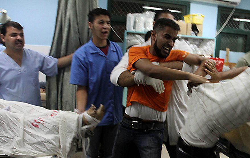 Palestinians react over one of three dead bodies of Islamic Jihad militants at the treatment room of Al-Aqsa hospital in Deir el-Balah, central Gaza Strip, Tuesday, Sept. 28, 2010.  The three Palestinian militants were killed late Monday in a clash with Israeli soldiers, both sides said. The Israelis said their forces fired at militants near the border of central Gaza as they were about to launch rockets at Israel. (AP Photo/Ashraf Amra)