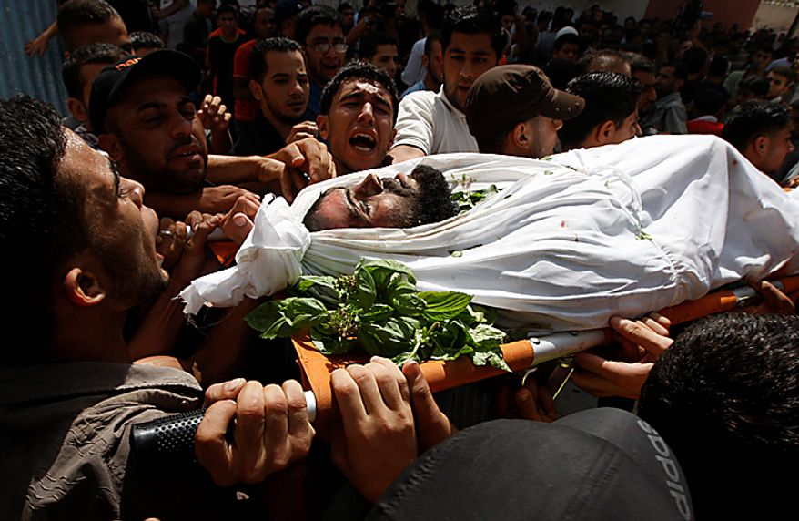 Palestinian mourners carry the body of Palestinian militant, Alaa Abu Z'beida, out of the family house during his funeral in Al Bureij refugee camp, central Gaza Strip, Tuesday, Sept. 28, 2010. Alaa Abu Z'beida and two other Palestinian militant were killed late Monday in a clash with Israeli soldiers. The Israelis said their forces fired at militants near the border of central Gaza as they were about to launch rockets at Israel. A small, al-Qaida-inspired group claimed responsibility on Tuesday. (AP Photo/Khalil Hamra)
