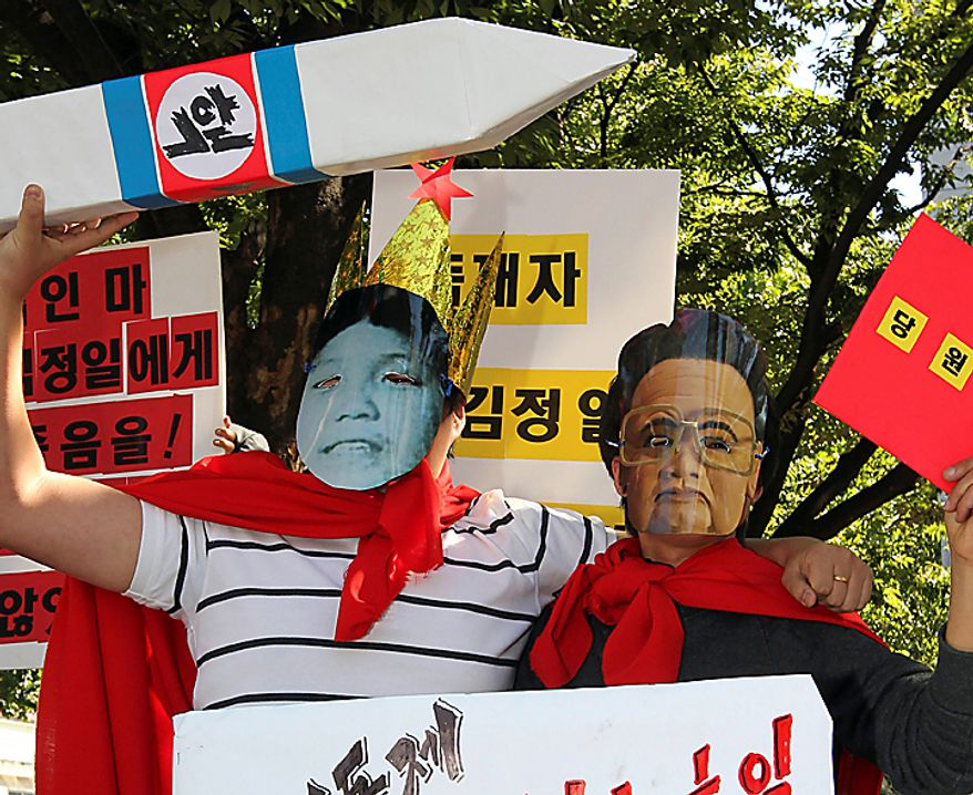 South Korean protesters wearing masks of North Korean leader Kim Jong-il, right,  and what protesters say is Kim's youngest son Kim Jong Un hold a mock nuclear missile during a rally against the North's succession in Seoul, South Korea, Tuesday, Sept. 28, 2010. North Korea's absolute leader Kim appointed his youngest son as an army general, giving the son his first known official title in an apparent sign that he is being groomed as the country's next leader. (AP Photo/Yonhap, Lim Hun-jung)