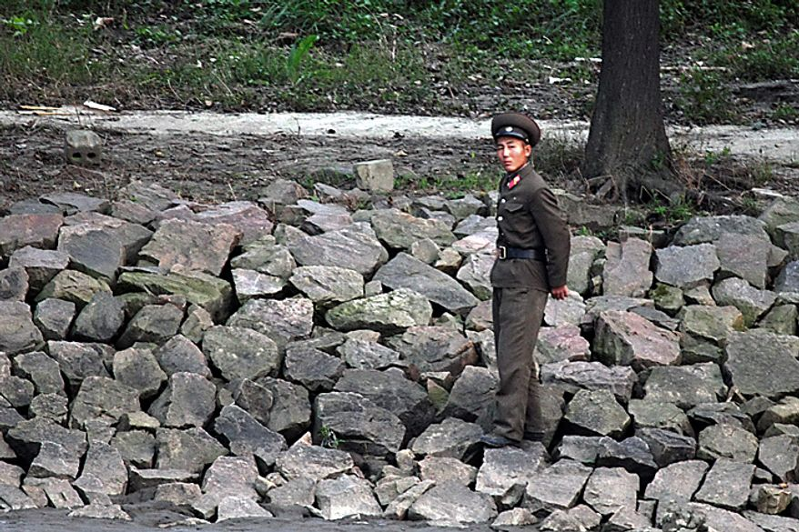 In this Sunday, Sept. 26 photo, a North Korean soldier walks on the bank of the Yalu River in the North Korean town of Sinuiju. North Korean leader Kim Jong Il promoted his youngest son to the rank of general in the Korean People's Army, the state news agency reported early Tuesday, the clearest signal yet that the 20-something is on track to succeed his father in ruling the impoverished country.  (AP Photo)