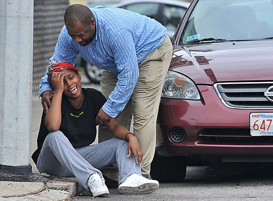A man comforts a grieving woman near the scene of a shooting in the Mattapan neighborhood of Boston, Tuesday, Sept. 28, 2010.  Five people, including a toddler, were shot, according to police. (AP Photo/Josh Reynolds)