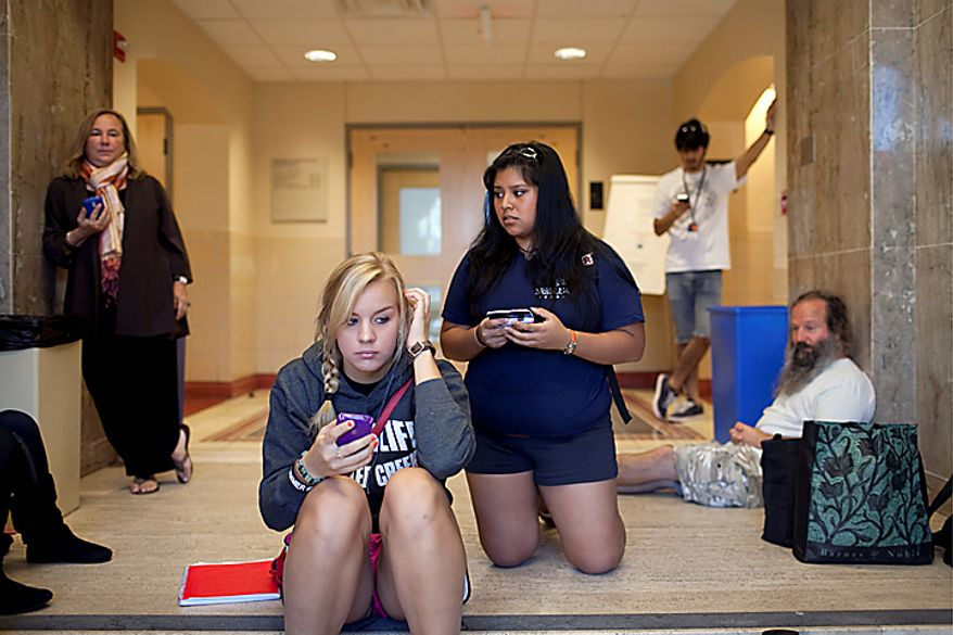 Students Paige Raiczyk, front left, and Veronica Rivera, front right and other University of Texas students and faculty hold their phones for updated text messages inside Benedict Hall on campus in Austin early Tuesday morning Sept. 28, 2010 after a shooting on campus.  A gunman opened fire Tuesday inside a University of Texas campus library then fatally shot himself, and police are searching for a possible second suspect, university police said. (AP Photo/The Daily Texan, Tamir Kalifa)