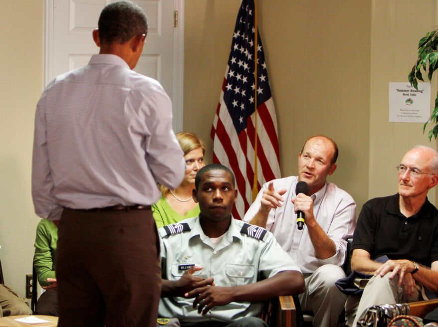 ASSOCIATED PRESS PHOTOGRAPHS President Obama listens to a question from Scott Turner (holding microphone) during a backyard meeting that, because of rain, had to be moved indoors at Southampton Recreation Center in Richmond, Va., on Wednesday.