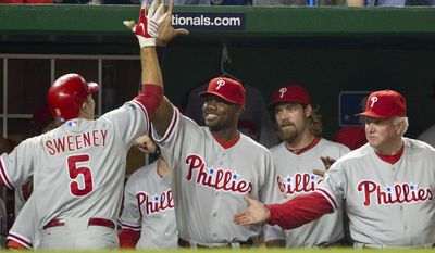 ASSOCIATED PRESS Philadelphia Phillies' Mike Sweeney, left, is congratulated by teammates, from left to right, Ryan Howard, Jayson Werth, and manager Charlie Manuel after hitting a solo home run against the Washington Nationals during the second inning of a baseball game on Wednesday, Sept. 29, 2010, in Washington.
