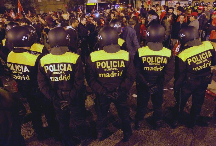 Police guard a bus depot in Madrid during a nationwide general strike organized by Spanish unions on Wednesday, Sept. 29, 2010. Picketers hurled eggs at buses and blocked trucks from delivering produce to wholesale markets as Spanish workers protested austerity measures imposed by a government struggling to slash its budget deficit and overcome recession. (AP Photo/Paul White)