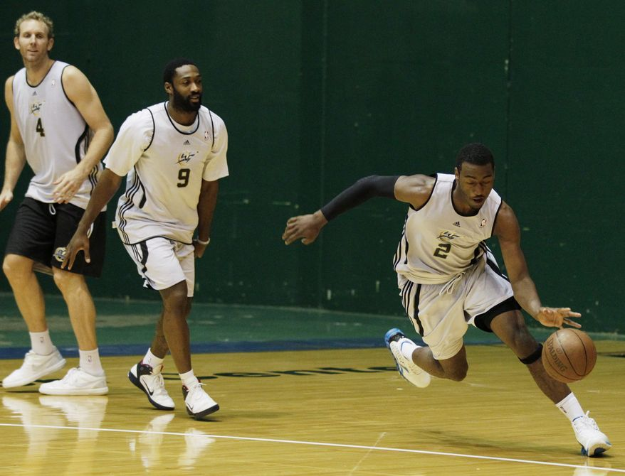 ASSOCIATED PRESS Washington Wizards' John Wall, righ, drives the ball as teammates Gilbert Arenas, center, and Sean Marks look on during NBA basketball training camp at the Patriot Center at George Mason University in Fairfax, Va., Wednesday, Sept. 29, 2010.