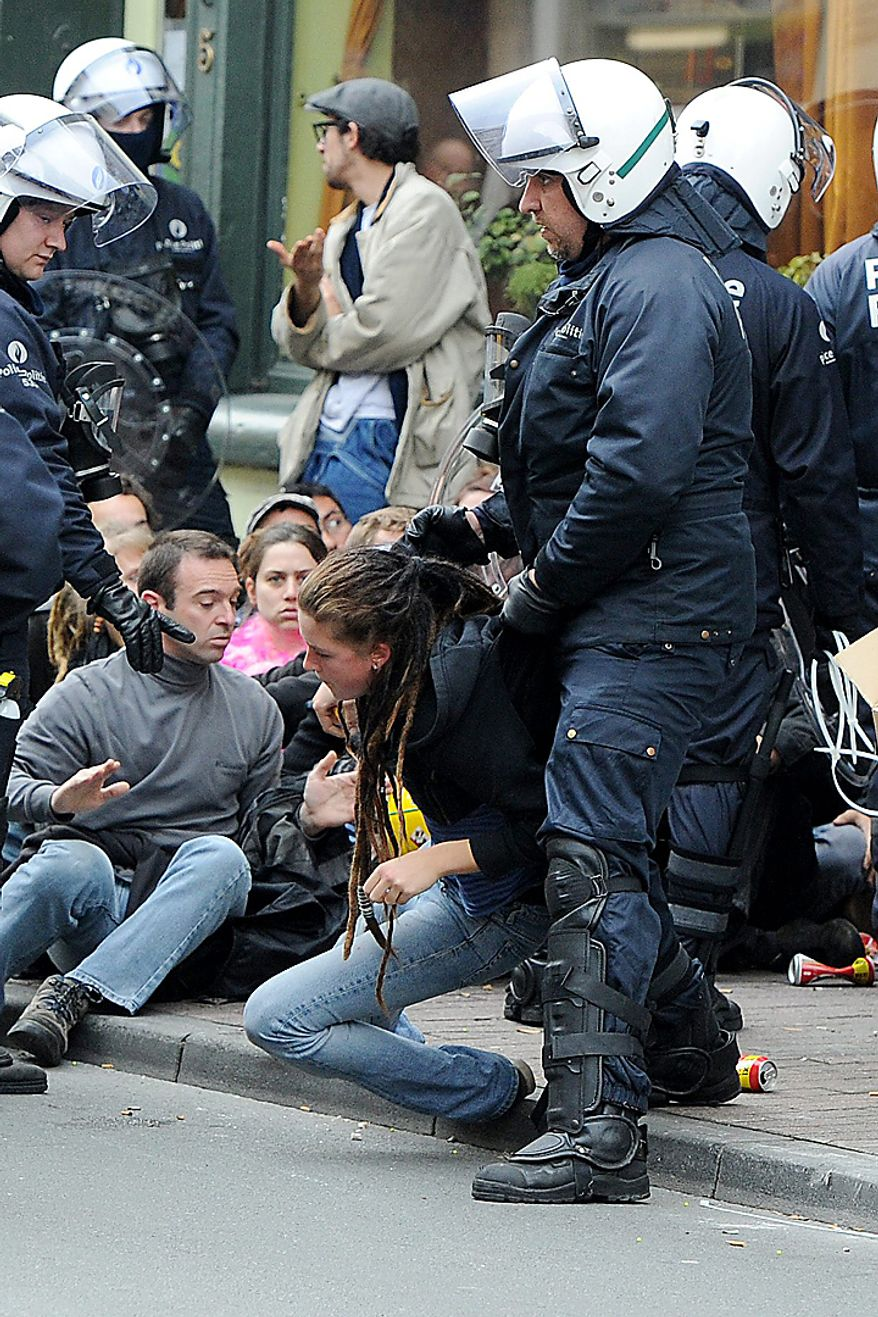 Riot police detain protesters in Brussels, Belgium on Wednesday, Sept. 29, 2010. Labor unions prepared a march of nearly 100,000 workers on the European Union institutions to protest the budget slashing plans and austerity measures of governments seeking to control spiraling debt. (AP Photo/Geert Vanden Wijngaert)