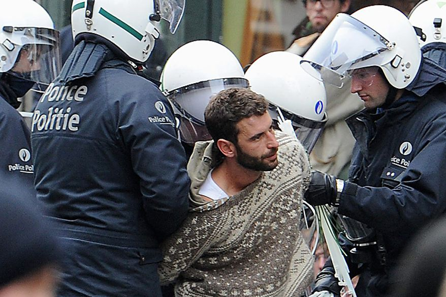 Riot police detain a protester in Brussels, Belgium on Wednesday, Sept. 29, 2010. Labor unions organized a march of nearly 100,000 workers of the European Union institutions to protest the budget slashing plans and austerity measures of governments seeking to control spiraling debt. (AP Photo/Geert Vanden Wijngaert)