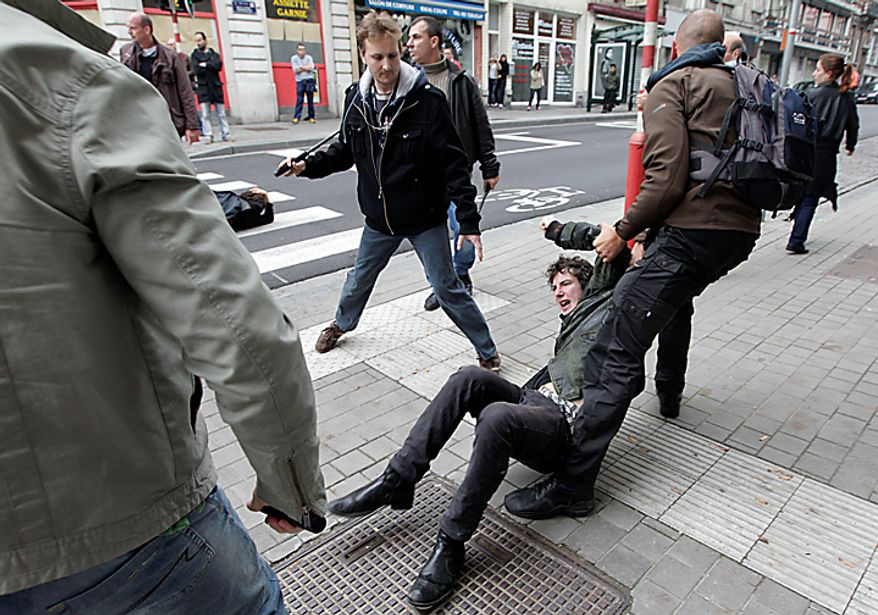 A protester is detained by plain clothes policemen, during a demonstration in Brussels, Belgium on Wednesday, Sept. 29, 2010. Labor unions organized a march of nearly 100,000 workers of the European Union institutions to protest the budget slashing plans and austerity measures of governments seeking to control spiraling debt. (AP Photo/Yves Logghe)