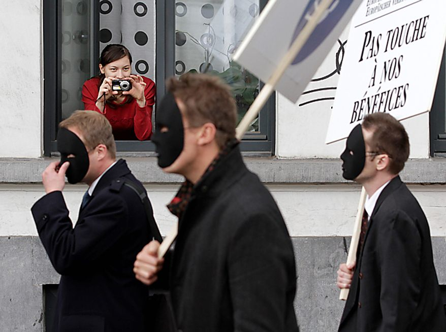 A woman takes a picture as demonstrators march down a main boulevard in Brussels, Belgium on Wednesday, Sept. 29, 2010. Labor unions organized a march of nearly 100,000 workers of the European Union institutions to protest the budget slashing plans and austerity measures of governments seeking to control spiraling debt. The ironic banner in French reads: 'Don't touch our profits'. (AP Photo/Yves Logghe)