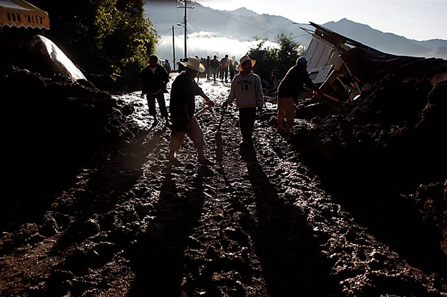 People remove mud from a street after a landslide in Santa Maria de Tlahuitoltepec, Mexico, Wednesday, Sept. 29, 2010. A mudslide first thought to have buried hundreds of people has left 11 missing and there are no confirmed deaths, authorities said Tuesday night, backing off earlier predictions of a catastrophe in Mexico's rain-soaked southern state of Oaxaca. (AP Photo/Miguel Tovar)