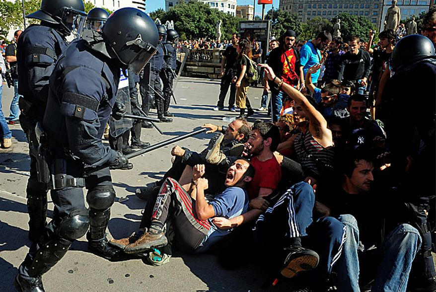 Riot police confront demonstrators during riots in Barcelona, on Wednesday, Sept. 29, 2010. Spanish workers staged a general strike Wednesday to protest austerity measures imposed by a government struggling to slash its budget deficit and overcome recession.(AP Photo/Manu Fernandez)