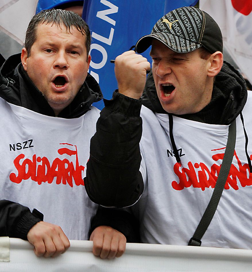 "Protesters wearing ""Solidarity"" tops shout slogans during a Solidarity trade union demonstration against budget cuts, in front of the Polish government office, in Warsaw, Poland, Wednesday, Sept. 29, 2010. About 6,000 protesters marched in rainy Warsaw in one of many demonstrations that took place across Europe to protest government austerity plans aimed at cutting deficits. (AP Photo/Czarek Sokolowski)"
