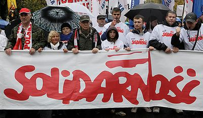 Protesters march behind a Solidarity banner during a Solidarity trade union demonstration against budget cuts, in front of the Polish government office, in Warsaw, Poland, Wednesday, Sept. 29, 2010. About 6,000 protesters marched in rainy Warsaw in one of many demonstrations that took place across Europe to protest government austerity plans aimed at cutting deficits. (AP Photo/Czarek Sokolowski)