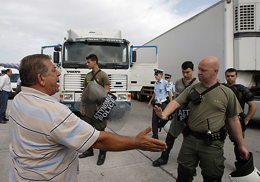 A protesting truck driver argues with policeman, left, after officers inspected vehicles during a demonstration at a highway toll station, in Elefsina , near Athens, on Wednesday, Sept. 29, 2010. Greece has already endured two weeks of protests by truck drivers who have made it difficult for businesses to get supplies. Bus and trolley drivers walked off the job for several hours while Athens' metro system and tram were to shut down at noon. National railway workers walked off the job at noon, disrupting rail connections across the country, while doctors at state hospitals went on a 24-hour strike.(AP Photo/Petros Giannakouris)