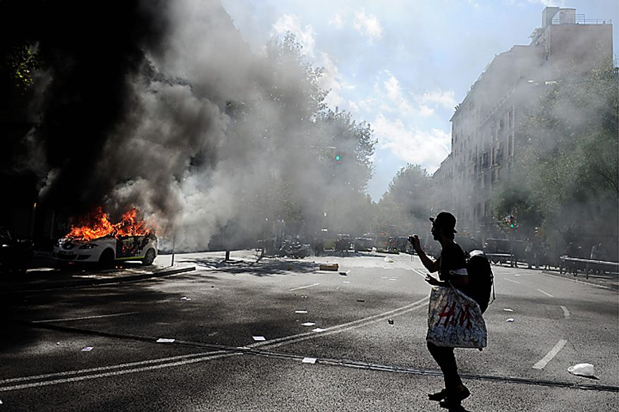 A demonstrator takes pictures of a burning police car during riots in Barcelona, Wednesday, Sept. 29, 2010. Spanish workers staged a general strike Wednesday to protest austerity measures imposed by a government struggling to slash its budget deficit and overcome recession. (AP Photo/David Ramos)