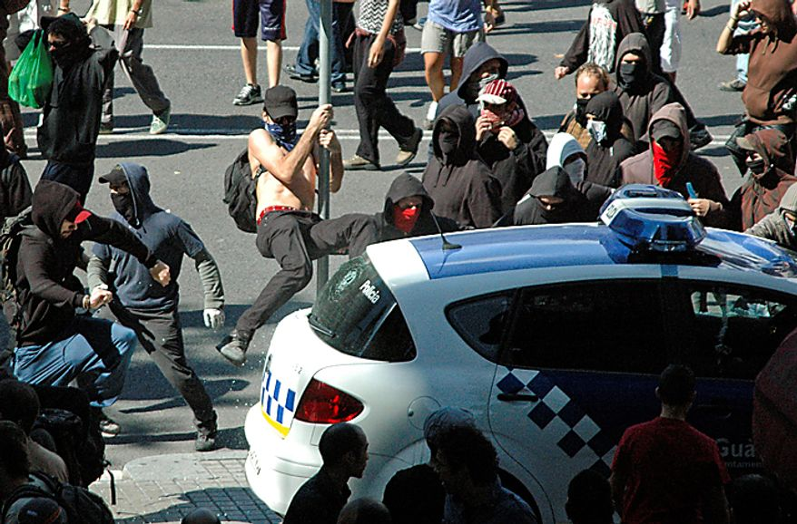 Protesters vandalize a police car during riots in Barcelona on Wednesday, Sept. 29, 2010. Shortly after, the car was set on fire. Spanish workers staged a general strike Wednesday to protest austerity measures imposed by a government struggling to slash its budget deficit and overcome recession. (AP Photo/Paula Fernandez)