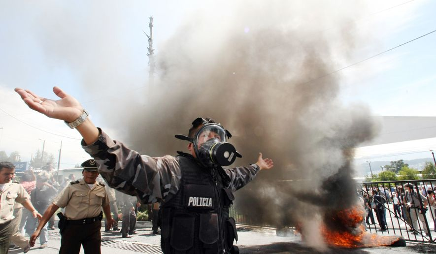 A policeman demonstrates Thursday at a police base in Quito, Ecuador, next to a bonfire during a protest of police officers and soldiers against a new law that cuts their benefits. President Rafael Correa tried to speak to a group of protesting police officers but was shouted down. (Associated Press)