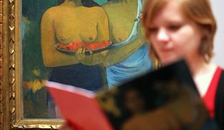 A woman looks at a catalogue in front of  ''Two Tahitian Women', artwork by French artist Paul Gauguin, at the Gauguin: Maker of Myth exhibition, at the Tate Modern, in London, Tuesday Sept. 28, 2010. (AP Photo/Katie Collins/PA)