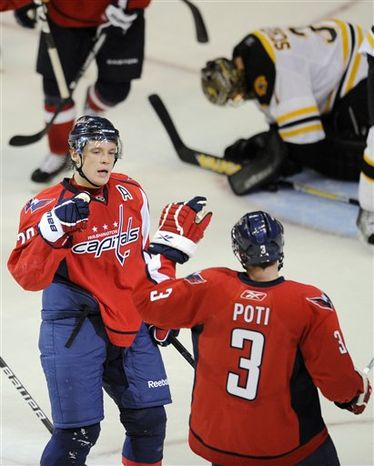 Washington Capitals' Alex Ovechkin, left, of Russia, chases the puck, next to Boston Bruins' Matt Hunwick (48) during the first period of an NHL hockey preseason game Tuesday, Sept. 28, 2010, in Washington. (AP Photo/Nick Wass)