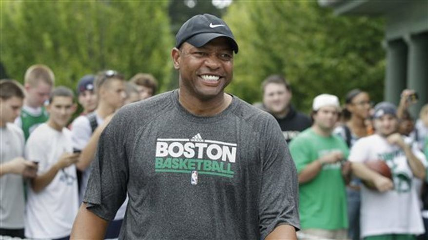 Boston Celtics head coach Doc Rivers smiles as he passes students after their practice at the team's training camp at Salve Regina University in Newport, R.I., Tuesday, Sept. 28, 2010.(AP Photo/Charles Krupa)