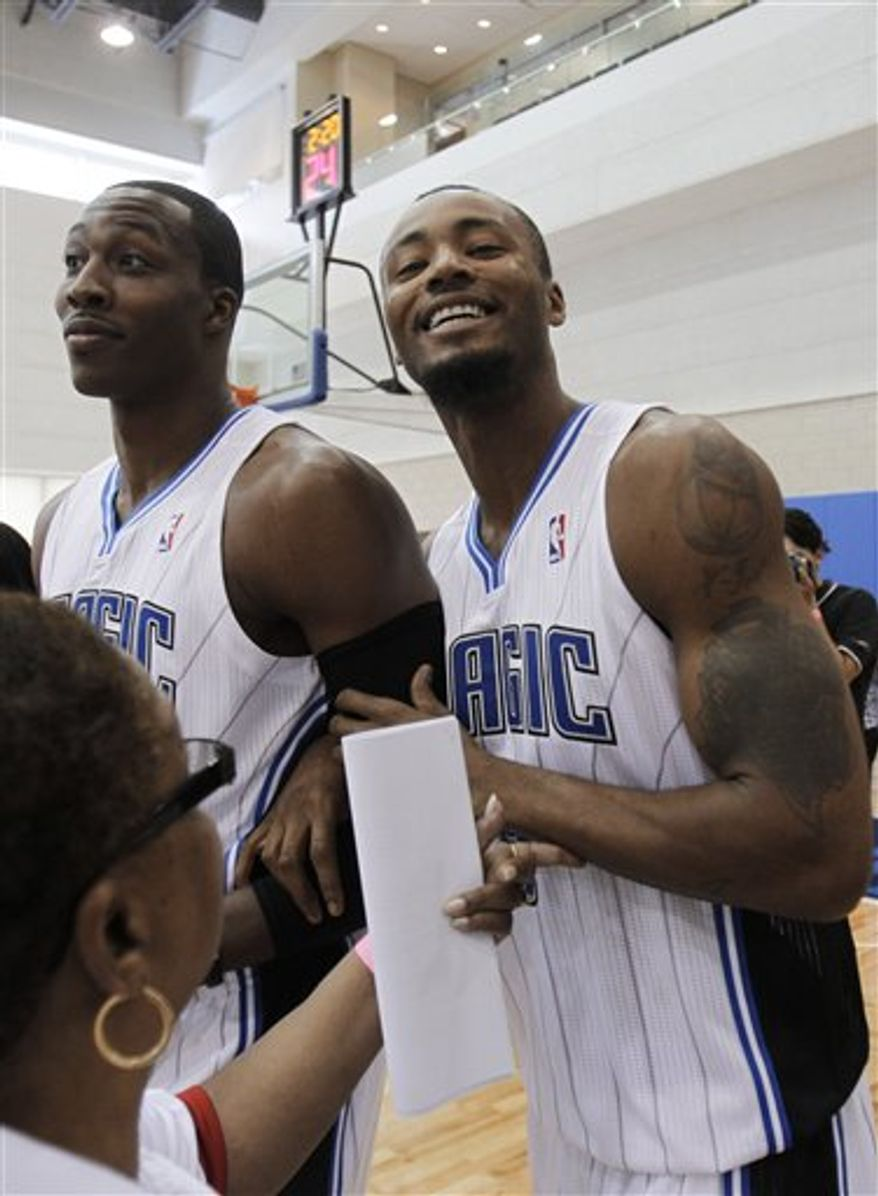 Orlando Magic's Dwight Howard, left, and Rashard Lewis, right, joke around with photographers and reporters as they come out onto the court for the NBA basketball team's media day in Orlando, Fla., Monday, Sept. 27, 2010. (AP Photo/John Raoux)
