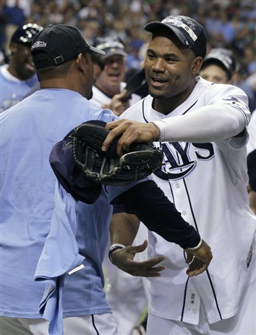 Baltimore Orioles second baseman Brian Roberts (1) and Mark Reynolds (12) high-five bench coach Willie Randolph, left, after the team defeated the Tampa Bay Rays 4-1 during an MLB baseball game on Friday, April 1, 2011, in St. Petersburg, Fla. (AP Photo/Chris O'Meara)