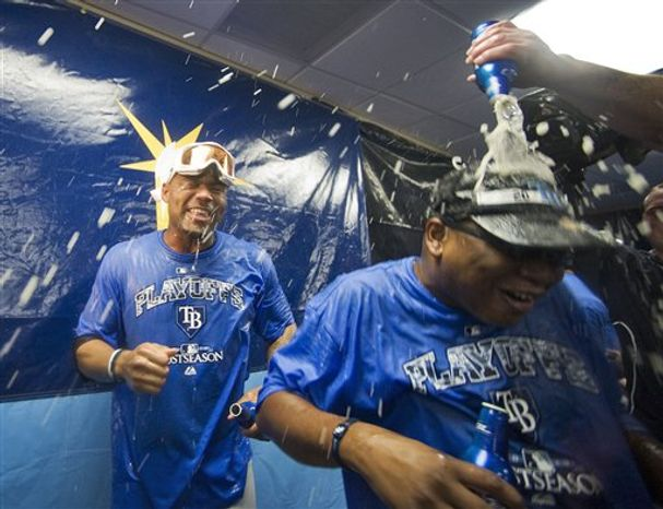 Tampa Bay Rays executive vice president of baseball operations Andrew Friedman, left, celebrates with Matt Garza, front, and others in the clubhouse after the Rays beat the Baltimore Orioles 5-0 in a baseball game to clinch a playoff spot Tuesday night, Sept. 28, 2010, in St. Petersburg, Fla. (AP Photo/Steve Nesius)