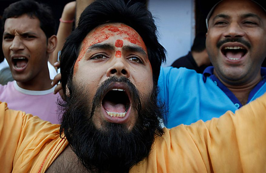 A Hindu priest shouts slogans as he celebrates after hearing the first reports on the court verdict in Ayodhya, India, Thursday, Sept. 30, 2010. An Indian court ruled Thursday that a disputed holy site that has sparked bloody communal riots across the country in the past should be divided between the Hindu and Muslim communities. However, the court gave the Hindu community control over the section where the now demolished Babri Mosque stood and where a small makeshift tent-shrine to the Hindu god Rama rests. While both Muslim and Hindu lawyers vowed to appeal to the Supreme Court, the compromise ruling seemed unlikely to set off a new round of violence, as the government had feared.  (AP Photo/Rajesh Kumar Singh)