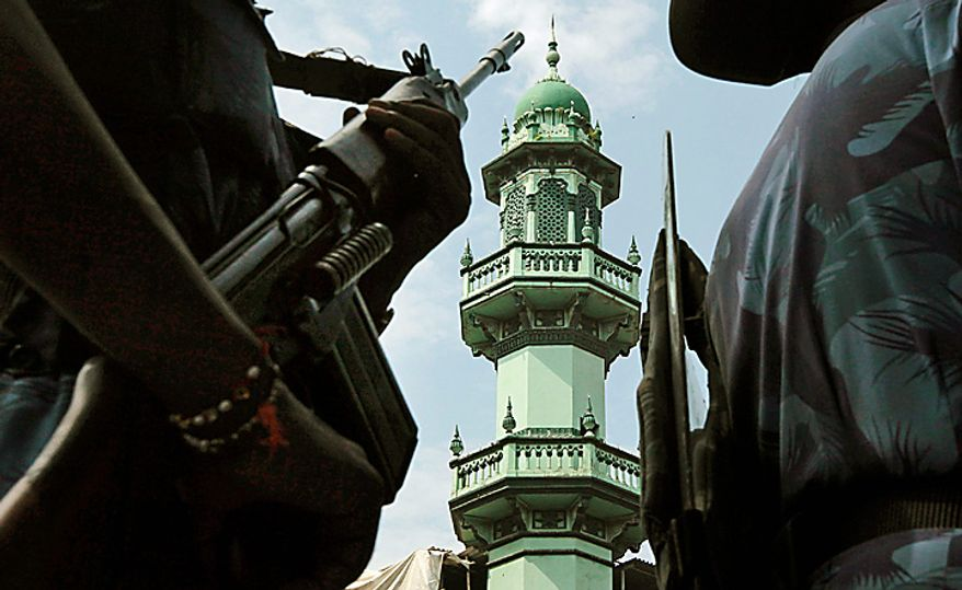India's Rapid Action Force soldiers patrol in front of a mosque in Mumbai, India, Thursday, Sept. 30, 2010. An Indian court ruled Thursday that a disputed holy site in Ayodhya that has sparked bloody communal riots across the country in the past should be divided between the Hindu and Muslim communities, a lawyer involved in the suit said.  The Muslim community said it would appeal the ruling in the 60-year-old case to the Supreme Court. Muslims revere the compound in Ayodhya as the site of the now-demolished 16th century Babri Mosque, while Hindus say it is the birthplace of the god Rama. (AP Photo/Rajanish Kakade)
