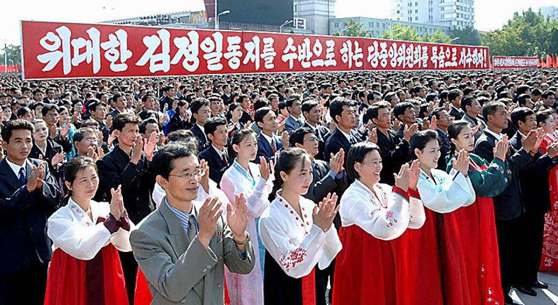 "In this Thursday, Sept. 30, 2010 photo released by Korean Central News Agency via Korea News Service in Tokyo, North Koreans clap hands during a ceremony hosted by the Pyongyang city to celebrate the re-election of their leader Kim Jong Il to the ruling party's top position, general secretary of the Workers' Party of Korea, at Kim Il Sung Square in Pyongyang, North Korea. The slogan reads: ""Let's defend the party's central committee headed by Dear Leader Kim Jong Il by risking our lives!"" AP Photo/Korean Central News Agency via Korea News Service)"