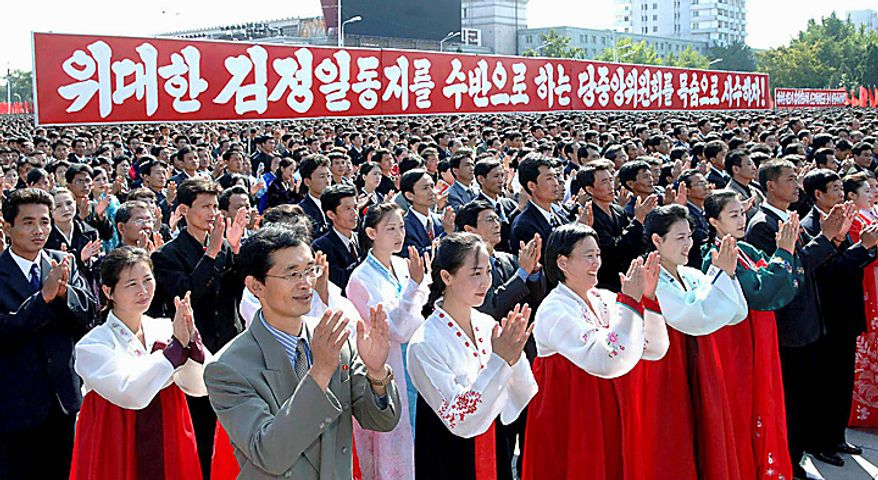 """In this Thursday, Sept. 30, 2010 photo released by Korean Central News Agency via Korea News Service in Tokyo, North Koreans clap hands during a ceremony hosted by the Pyongyang city to celebrate the re-election of their leader Kim Jong Il to the ruling party's top position, general secretary of the Workers' Party of Korea, at Kim Il Sung Square in Pyongyang, North Korea. The slogan reads: """"Let's defend the party's central committee headed by Dear Leader Kim Jong Il by risking our lives!"""" AP Photo/Korean Central News Agency via Korea News Service)"""