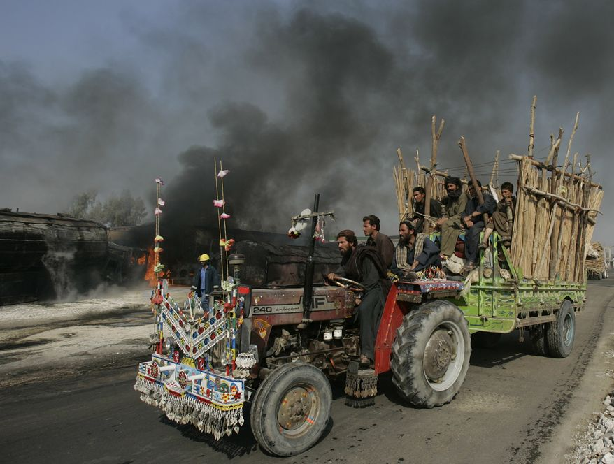 Pakistani flood affected residents pass by the still smoldering oil trucks in Shikarpur, southern Pakistan on Friday Oct. 1, 2010. Suspected militants set ablaze at least 27 tankers carrying fuel for U.S. and NATO troops in Afghanistan on Friday, police said. (AP Photo/Aaron Favila)