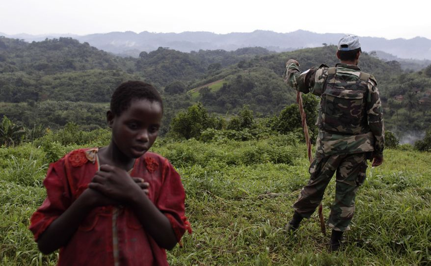 ** FILE ** In this Oct. 2, 2009, file photo, a Congolese girl walks past a Uruguayan United Nations peacekeeper as he stands watch on a hill near a peacekeeper encampment in Kimua in the heart of territory held by Rwandan Hutu rebels in eastern Congo. Congolese community leaders say they warned local U.N. officials and army commanders of the dangers and begged them to protect villagers days before rebels gang-raped scores of people from a month-old baby boy to a 110-year-old great-great-grandmother. (AP Photo/Rebecca Blackwell, File)