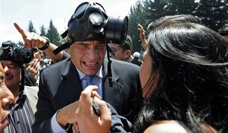 With a gas mask on his head, Ecuador's President Rafael Correa, center, gestures as he runs away from tear gas during a protest of police officers and soldiers against a new law that cuts their benefits at a police base in Quito, Ecuador, Thursday, Sept. 30, 2010. There were no reports of serious violence against the government, but Correa was hospitalized due to the effects of tear gas after being shouted down and pelted with water as he tried to speak with a group of police protesters. (AP Photo/Patricio Realpe)
