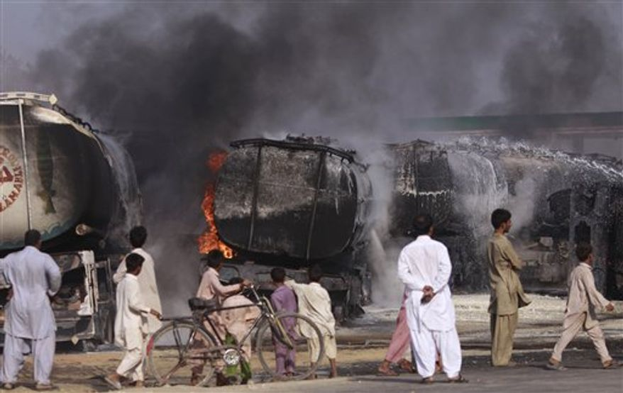 Pakistani residents walk by the still smoldering oil trucks in Shikarpur, southern Pakistan on Friday Oct. 1, 2010. Suspected militants set ablaze at least 27 tankers carrying fuel for U.S. and NATO troops in Afghanistan on Friday, police said. (AP Photo/Aaron Favila)