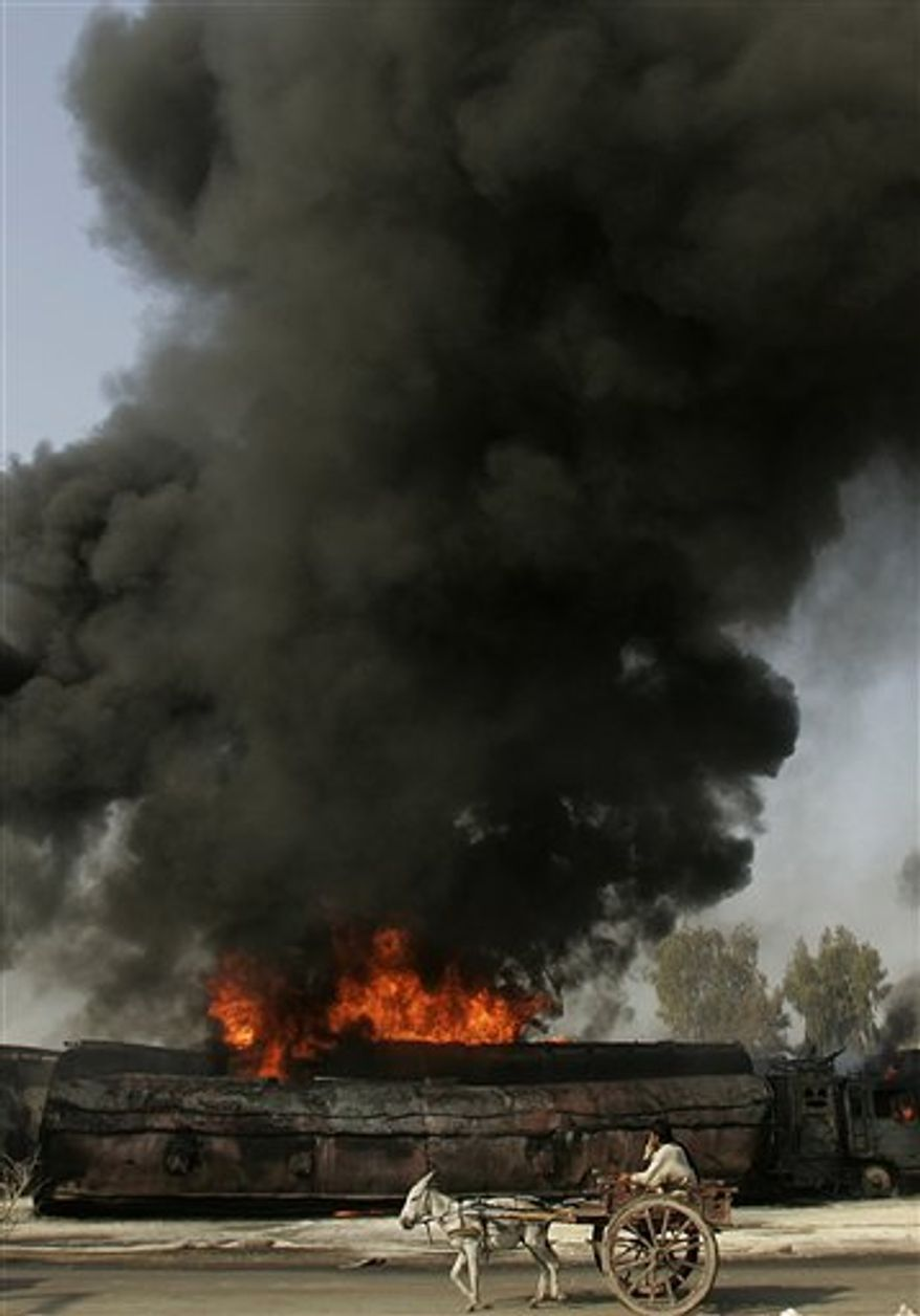 A Pakistani man on a donkey-drawn cart passes by a burning oil trucks in Shikarpur, southern Pakistan on Friday Oct. 1, 2010. Suspected militants set ablaze at least 27 tankers carrying fuel for U.S. and NATO troops in Afghanistan on Friday, police said. (AP Photo/Aaron Favila)